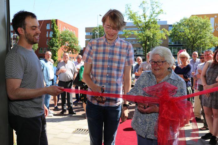 Het clubhuis wordt geopend met het doorknippen van een rood lint door Rimmert Riedstra (midden) en mevrouw Meijerman (rechts). Fotografie: Esther van Dokkum.